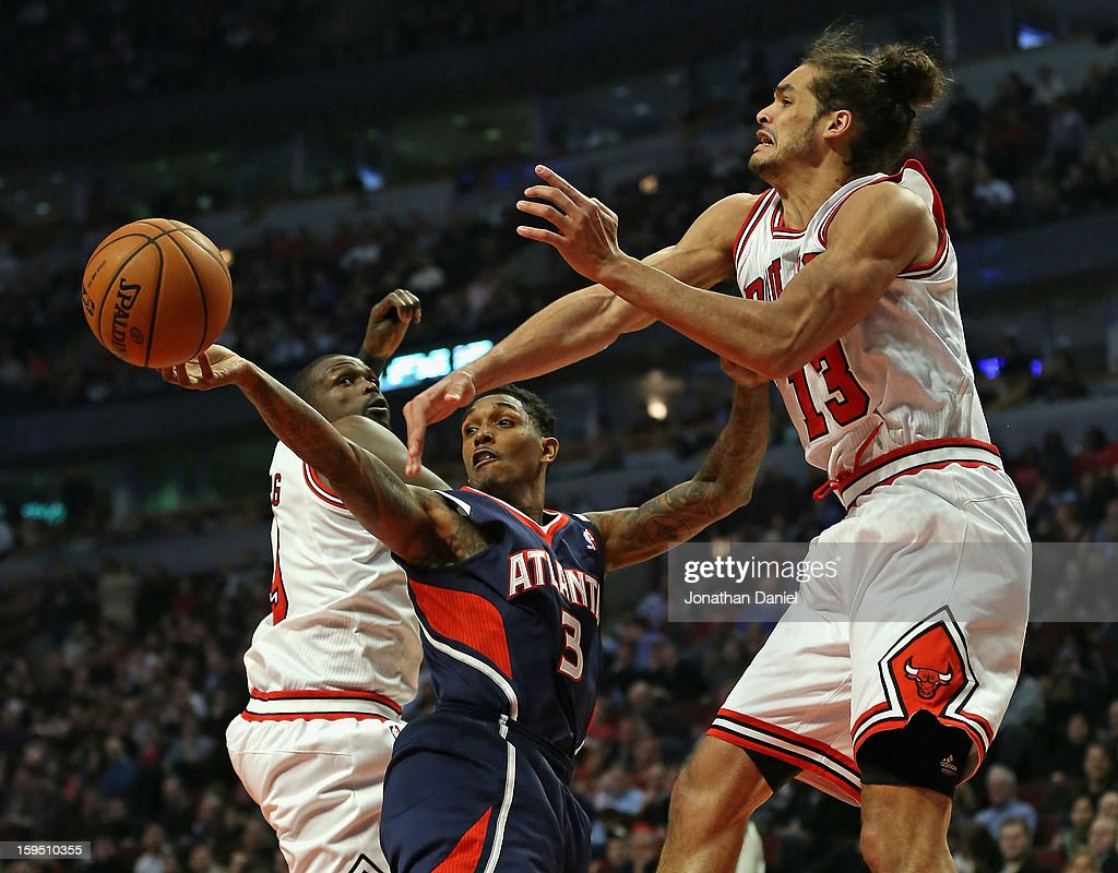 Louis Williams #3 of the Atlanta Hawks passes between Loul Deng #9 and Joakim Noah #13 of the Chicago Bulls at the United Center on January 14, 2013 in Chicago, Illinois.