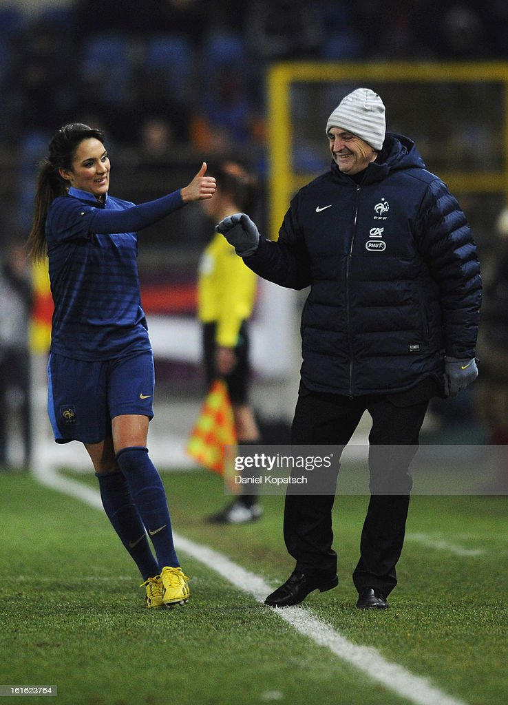 Louisa Necib of France (L) celebrates her team's second goal with head coach Bruno Bini during the international friendly match between France and Germany at Stade de la Meinau on February 13, 2013 in Strasbourg, France.
