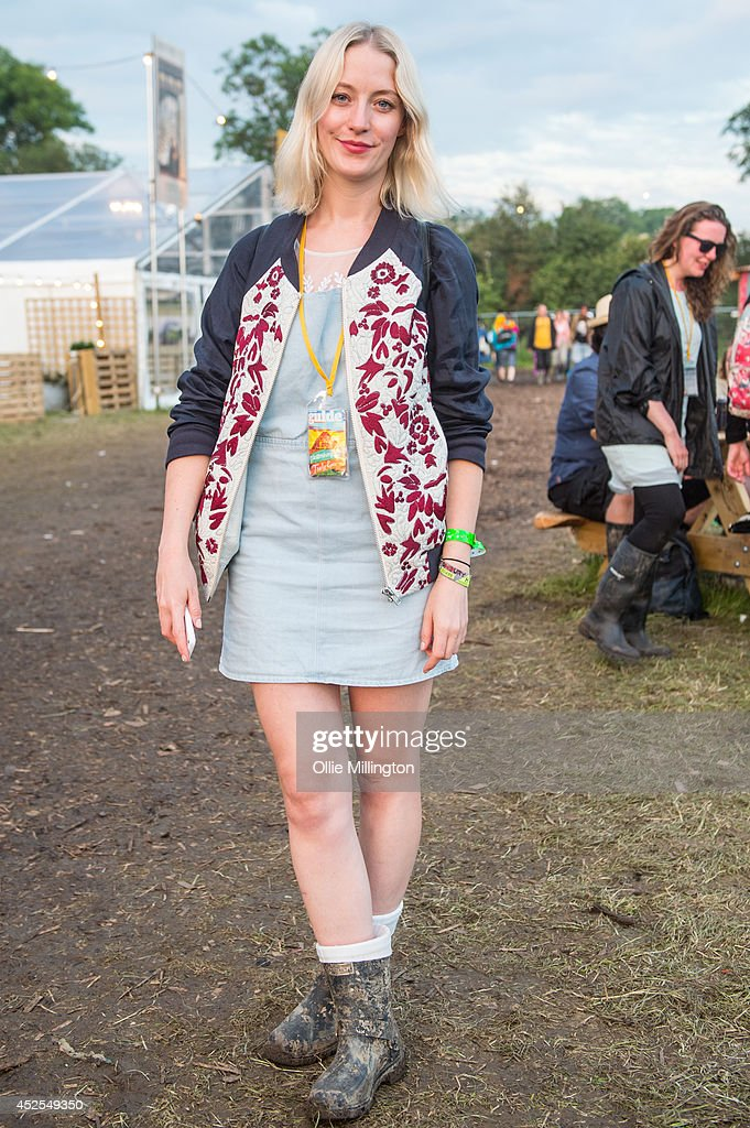 Louise 23, a journalist from London wearing a dress from H&M and a jacket from Topsop with limited edition Hunter wellies on the last day of the Glastonbury Festival at Worthy Farm on June 29, 2014 in Glastonbury, England.