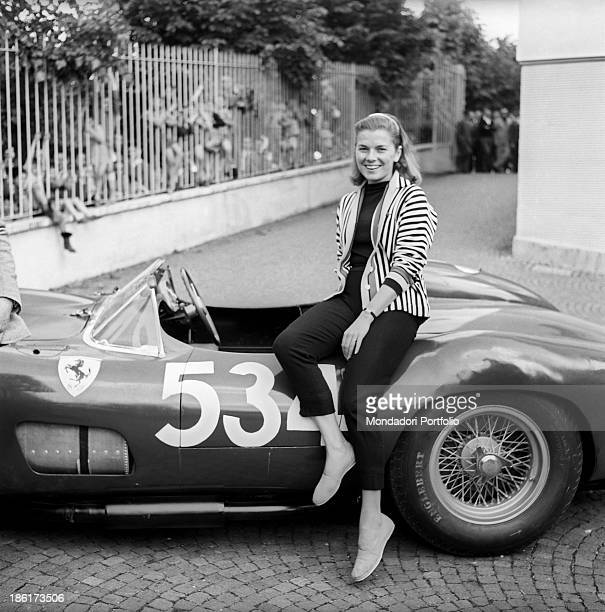 Louise Collins posing smiling leaned on the car driven by her husband and British racing driver Peter Collins at the Mille Miglia Automobile Race...