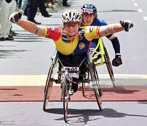 Louise Sauvage of Australia crosses the finish line just in front of Jean Driscoll of the US to win the women's wheelchair division of the 103rd...