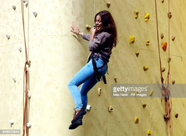 Louise Thompson from 'Made in Chelsea' climbing the 22m high Walkers Deep Ridged Crisp wall at launch of the new Walkers Deep Ridged crisps at The...