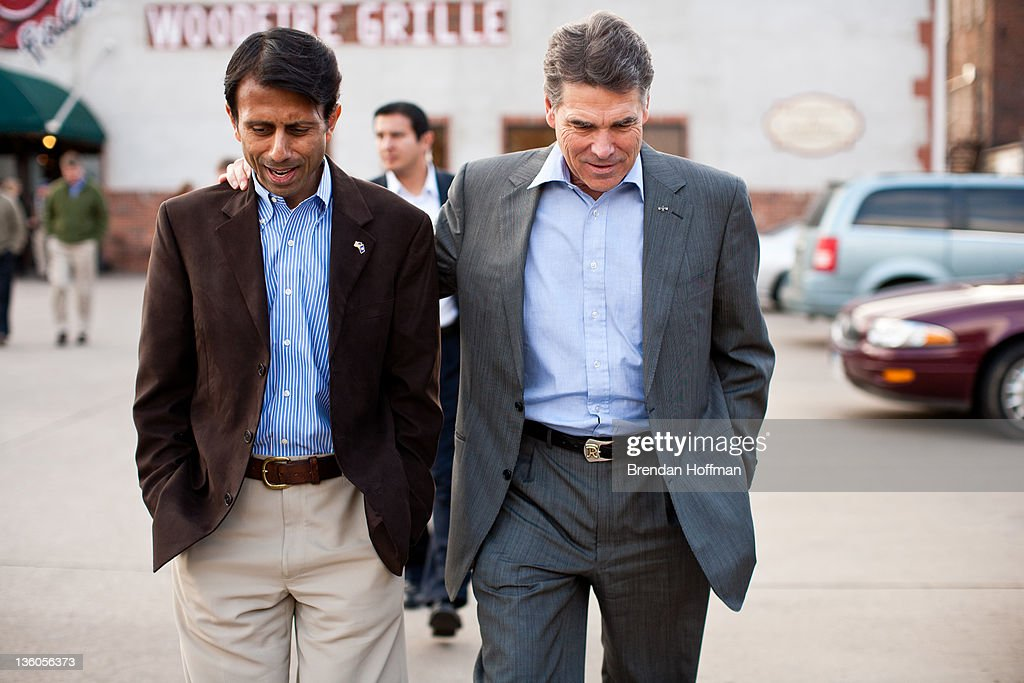 Louisiana Gov. <a gi-track='captionPersonalityLinkClicked' href=/galleries/search?phrase=Bobby+Jindal&family=editorial&specificpeople=2249969 ng-click='$event.stopPropagation()'>Bobby Jindal</a> (L) and Republican presidential candidate and Texas Gov. <a gi-track='captionPersonalityLinkClicked' href=/galleries/search?phrase=Rick+Perry+-+Politician&family=editorial&specificpeople=175872 ng-click='$event.stopPropagation()'>Rick Perry</a> walk together after a campaign meet and greet at The Button Factory restaurant on December 21, 2011 in Muscatine, Iowa. Perry is on a bus tour across Iowa to campaign before the caucuses.