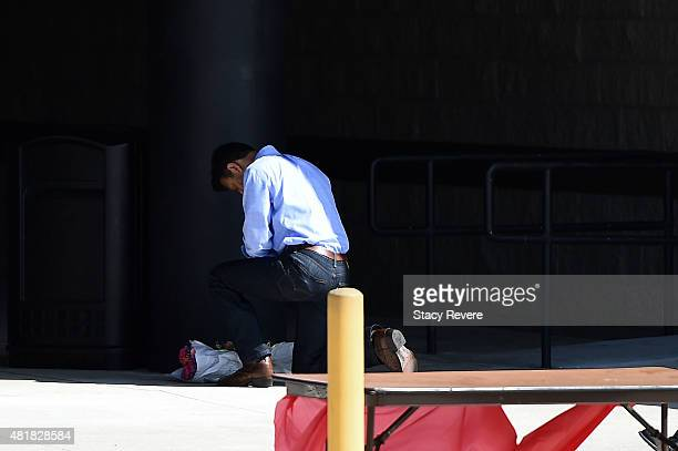 Louisiana Governor Bobby Jindal lays flowers outside of the Grand Theatre on July 24 2015 in Lafayette Louisiana Two people were killed and nine...