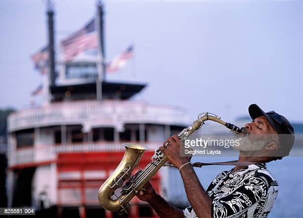 USA, Louisiana, New Orleans, saxophonist and paddle steamer