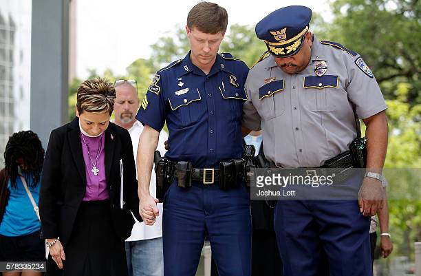 Louisiana State Police Officer Jared Sandifer center and Baton Rouge Police Lieutenant Terrance Watkins right pray during a vigil for Baton Rouge...