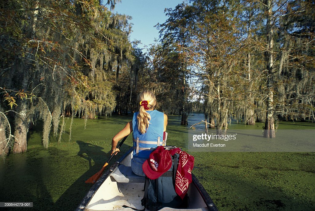 USA, Louisiana, woman canoeing on Lake Martin near Lafayette and Breaux Bridge, rear view : Stock Photo
