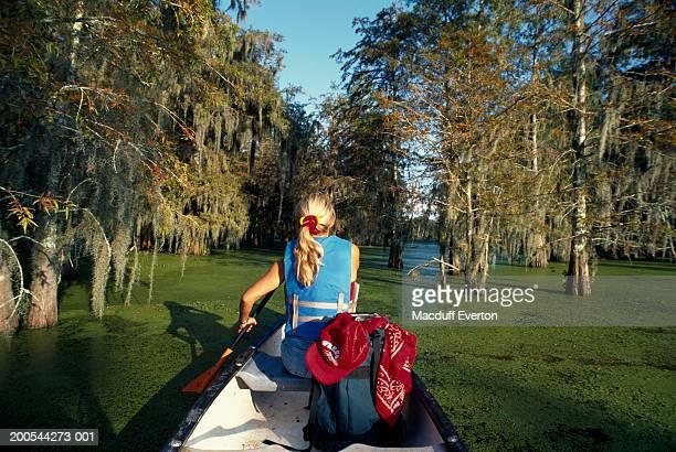 USA, Louisiana, woman canoeing on Lake Martin near Lafayette and Breaux Bridge, rear view