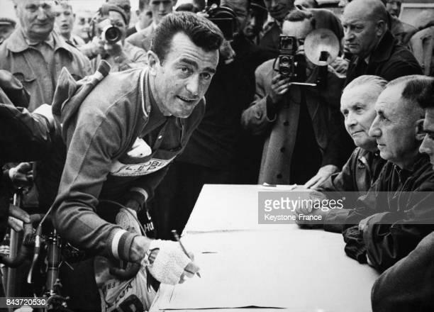 Louison Bobet signe au contrôle du départ du Tour de France à Bruxelles Belgique le 26 juin 1958