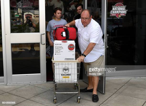 Louisville basketball equipment manager Vinny Tatum and two team managers use a cart to haul boxes out of Rick Pitino's office at the Yum Practice...