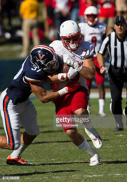 Louisville Cole Hikutini is tackled by Virginia Jordan Mack during an NCAA football game between the Louisville Cardinals and the Virginia Cavaliers...