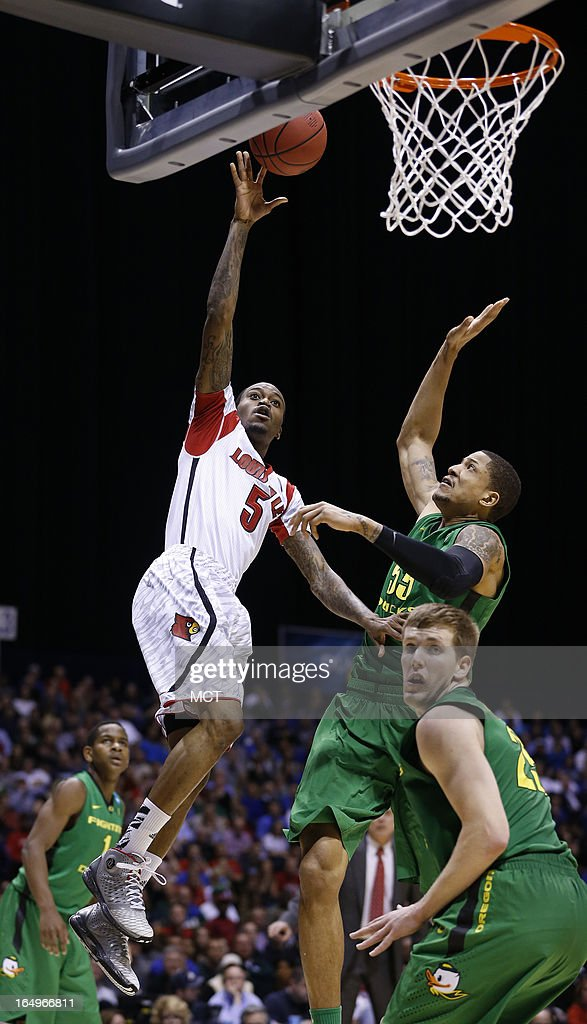 Louisville guard Kevin Ware goes to the basket past Oregon center Tony Woods in second half action in their NCAA fourth round game on Friday March 29...