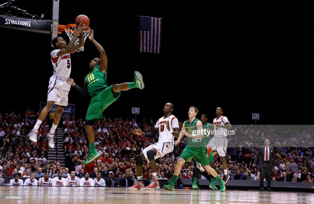 Louisville guard Kevin Ware looks to kick the ball out against pressure from Oregon guard Johnathan Loyd in second half action in their NCAA fourth...