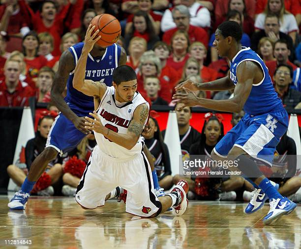 Louisville guard Peyton Siva tries to pass out of the trap of Kentucky guard DeAndre Liggins and guard Brandon Knight during game action at the KFC...