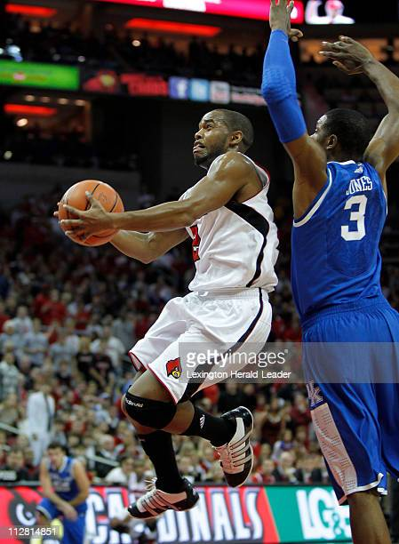 Louisville guard Preston Knowles goes under Kentucky forward Terrence Jones for a basket in the first half at the KFC Yum Center in Louisville...