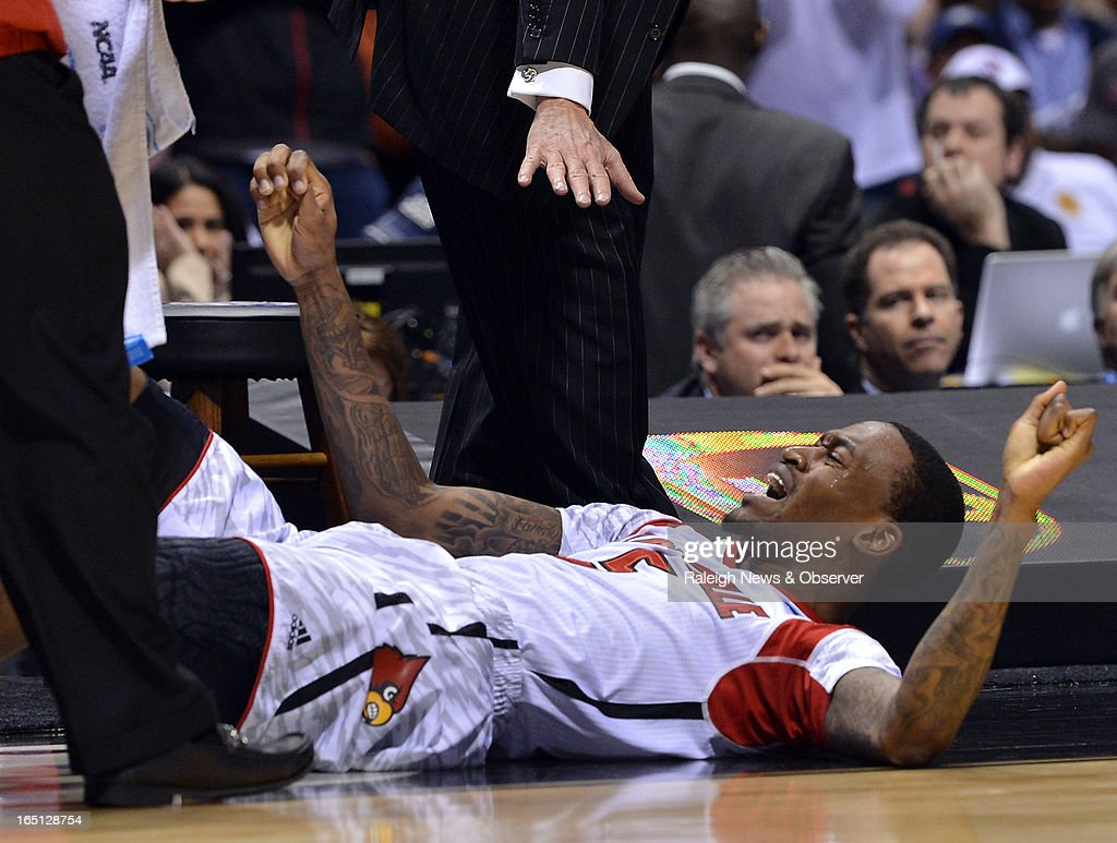 Louisville head coach Rick Pitino tells guard Kevin Ware (5) to stay down after he broke his leg in front of the bench in the first half of the NCAA Tournament at Lucas Oil Stadium in Indianapolis, Indiana, Sunday, March 31, 2013. Louisville defeated Duke, 85-63.