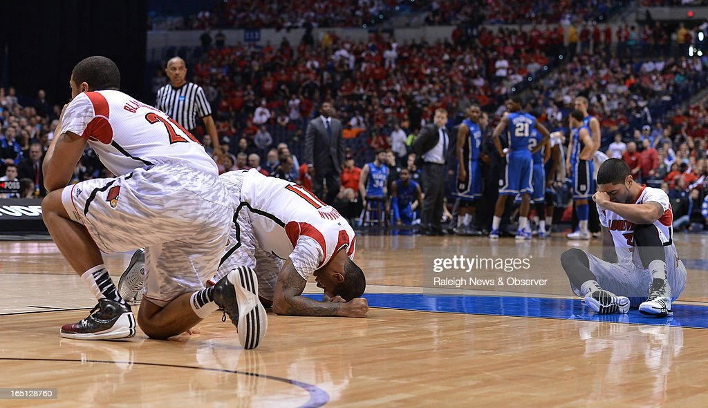 Louisville players collapse on the floor after teammate guard Kevin Ware (5) broke his leg in the first half of the NCAA Tournament at Lucas Oil Stadium in Indianapolis, Indiana, Sunday, March 31, 2013. Louisville defeated Duke, 85-63.