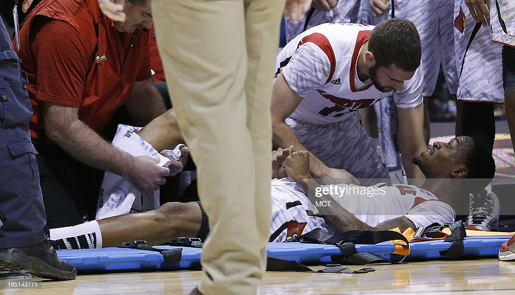 Louisville teammates gather around teammate Louisville guard Kevin Ware after he broke his right leg in first half action in the NCAA regional final...