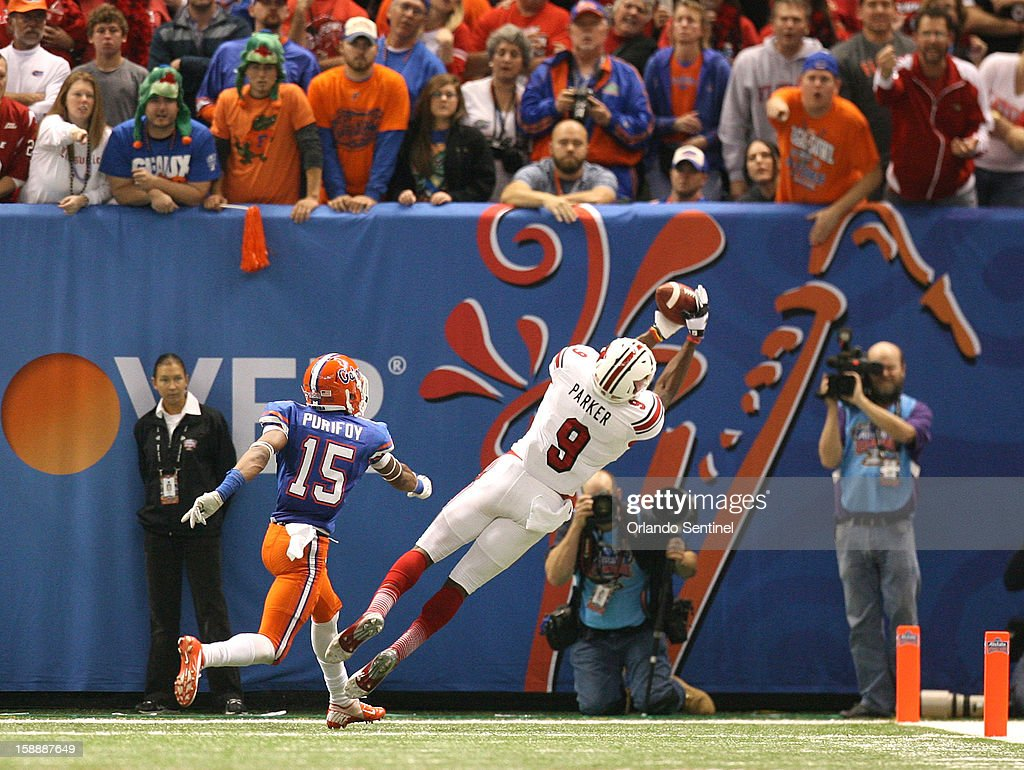 Louisville's Devante Parker hauls in a 15-yard touchdown pass as Florida's Loucheiz Purifoy (15) trails the play in the Allstate Sugar Bowl at the Mercedes-Benz Superdome on Wednesday, January 2, 2013, in New Orleans, Louisiana.