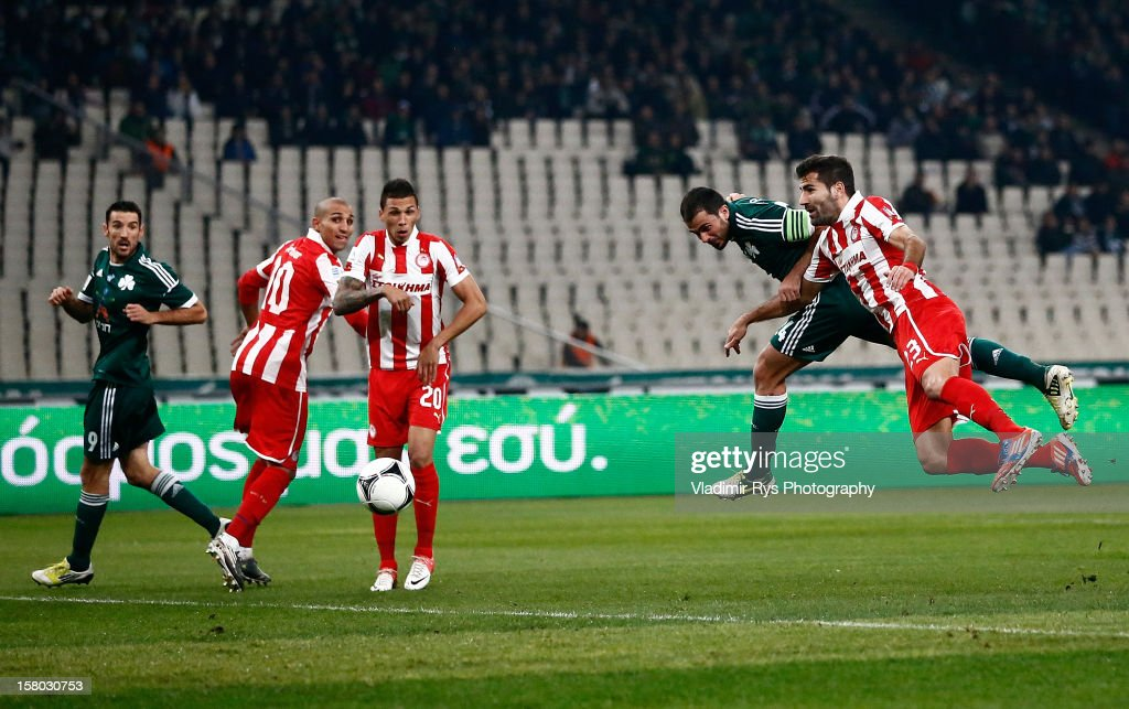 Loukas Vyntra of Panathinaikos and Dimitris Siovas of Olympiacos (R) vie for a header during the Superleague match between Panathinaikos FC and Olympiacos Piraeus at OAKA Stadium on December 9, 2012 in Athens, Greece.