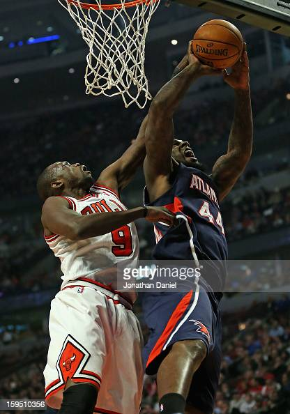 Loul Deng of the Chicago Bulls blocks a shot by Ivan Johnson of the Atlanta Hawks at the United Center on January 14 2013 in Chicago Illinois NOTE TO...