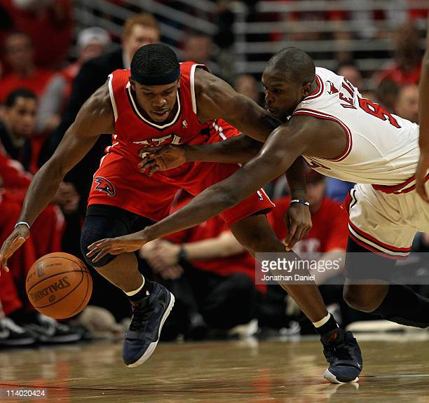 Loul Deng of the Chicago Bulls dives for the ball held by Joe Johnson of the Atlanta Hawks in Game Five of the Eastern Conference Semifinals in the...