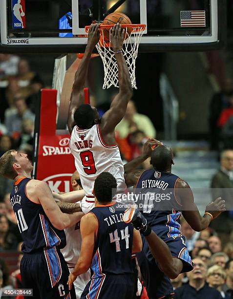 Loul Deng of the Chicago Bulls dunks over Cody Zeller Jeff Taylor and Bismack Biyombo of the Charlotte Bobcats at the United Center on November 18...