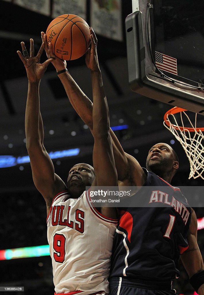 Loul Deng #9 of the Chicago Bulls grabs a rebound away from <a gi-track='captionPersonalityLinkClicked' href=/galleries/search?phrase=Tracy+McGrady&family=editorial&specificpeople=201486 ng-click='$event.stopPropagation()'>Tracy McGrady</a> #1 of the Atlanta Hawks at the United Center on January 3, 2012 in Chicago, Illinois. The Bulls defeated the Hawks 76-74.