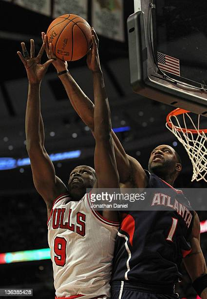 Loul Deng of the Chicago Bulls grabs a rebound away from Tracy McGrady of the Atlanta Hawks at the United Center on January 3 2012 in Chicago...