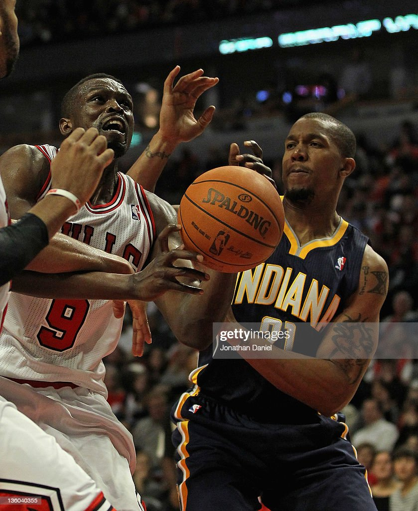 Loul Deng #9 of the Chicago Bulls is fouled as he tries to shoot under pressure from David West #21 of the Indiana Pacers at the United Center on December 20, 2011 in Chicago, Illinois. The Bulls defeated the Pacers 93-85.