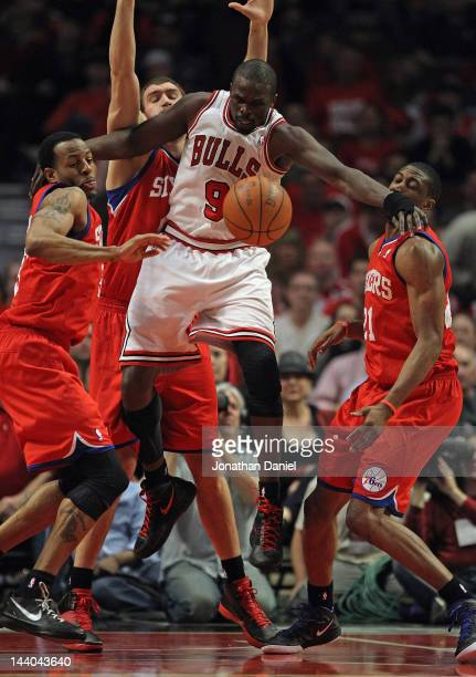 Loul Deng of the Chicago Bulls looses control of the ball under pressure from Andre Iguodala Spencer Hawes and Thaddeus Yound of the Philadelphia...