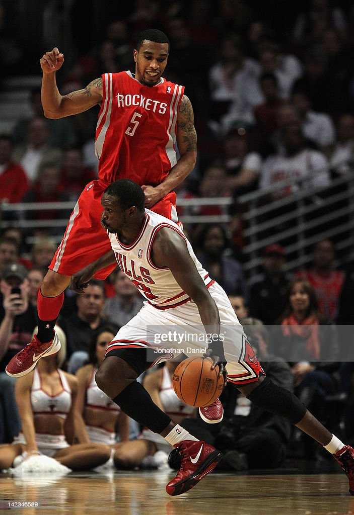 Loul Deng #9 of the Chicago Bulls moves against a leaping <a gi-track='captionPersonalityLinkClicked' href=/galleries/search?phrase=Courtney+Lee&family=editorial&specificpeople=730223 ng-click='$event.stopPropagation()'>Courtney Lee</a> #5 of the Houston Rockets at the United Center on April 2, 2012 in Chicago, Illinois.
