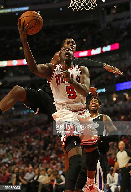 Loul Deng of the Chicago Bulls shoots under pressure from Jason Thompson of the Sacramento Kings at the United Center on October 31 2012 in Chicago...
