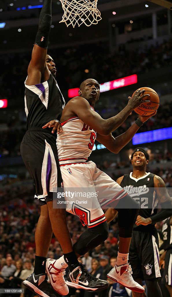 Loul Deng #9 of the Chicago Bulls shoots under pressure from Jason Thompson #34 of the Sacramento Kings at the United Center on October 31, 2012 in Chicago, Illinois. The Bulls defeated the Kings 93-87.
