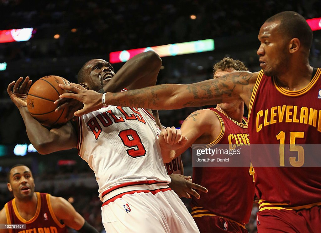 Loul Deng of the Chicago Bulls tries to control the ball under pressure from Marreese Speights and Luke Walton of the Cleveland Cavaliers at the...