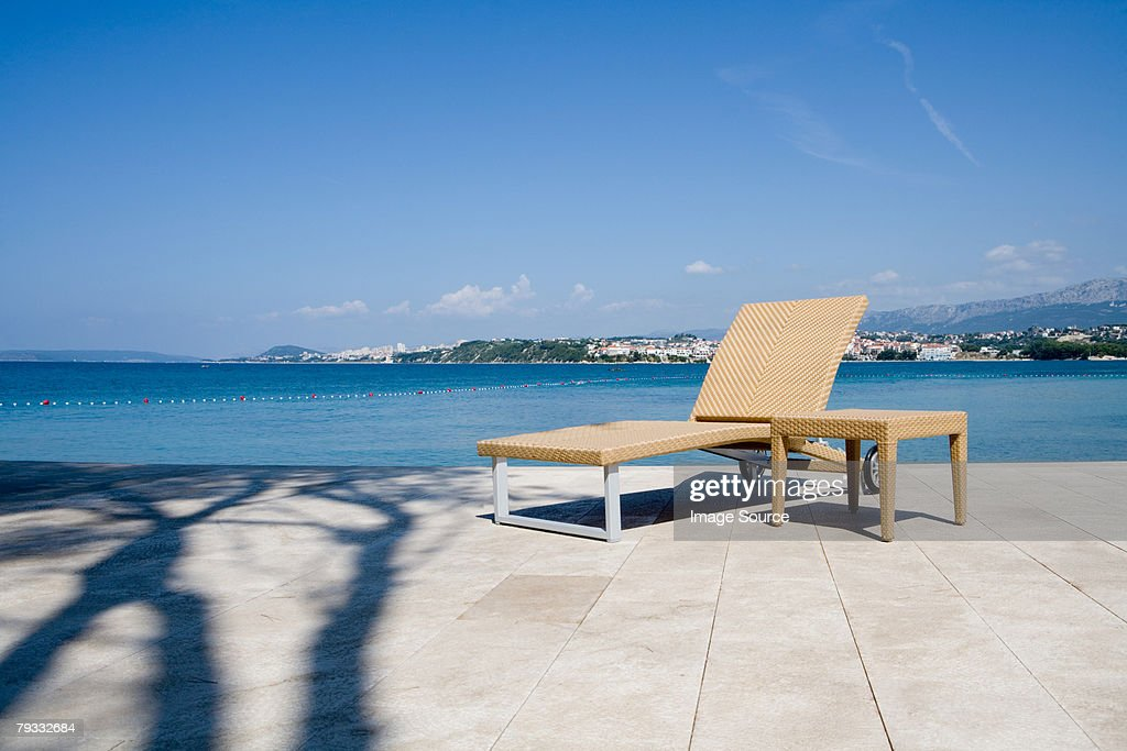 Lounge chair by the sea : Stock Photo