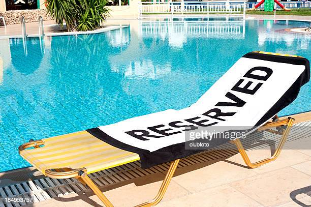 Lounge chair next to pool with 'Reserved' towel
