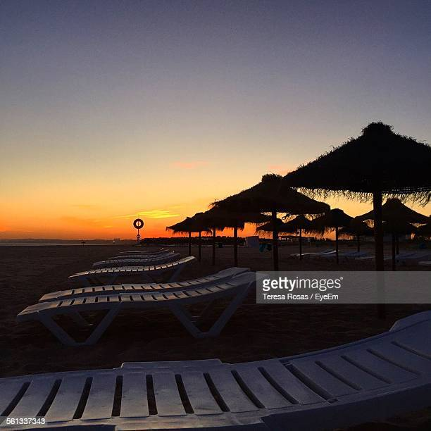 Lounge Chairs And Sunshades On Beach During Sunset