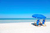 Two blue beach loungers and umbrella at white sandy beach