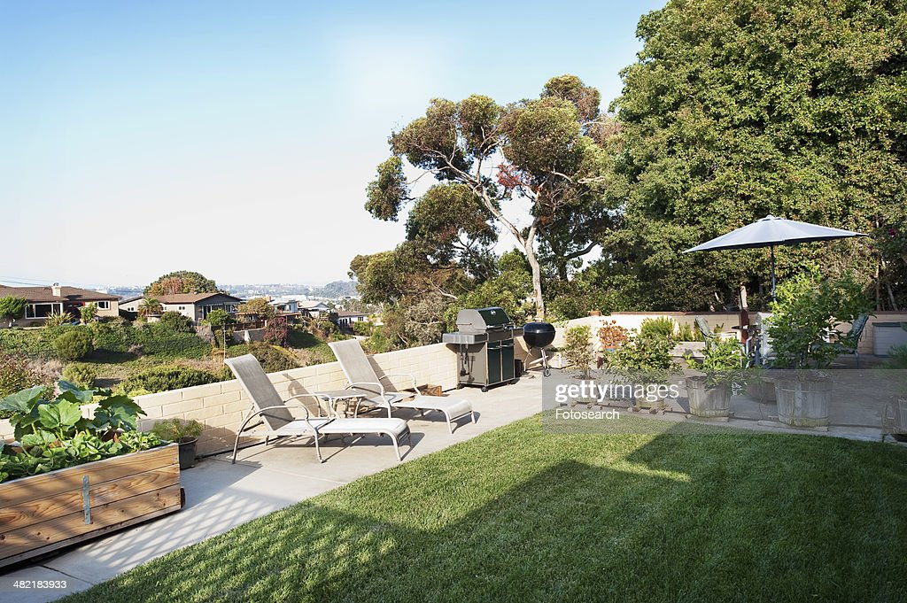 Lounge chairs, barbecue grills and plants in lawn