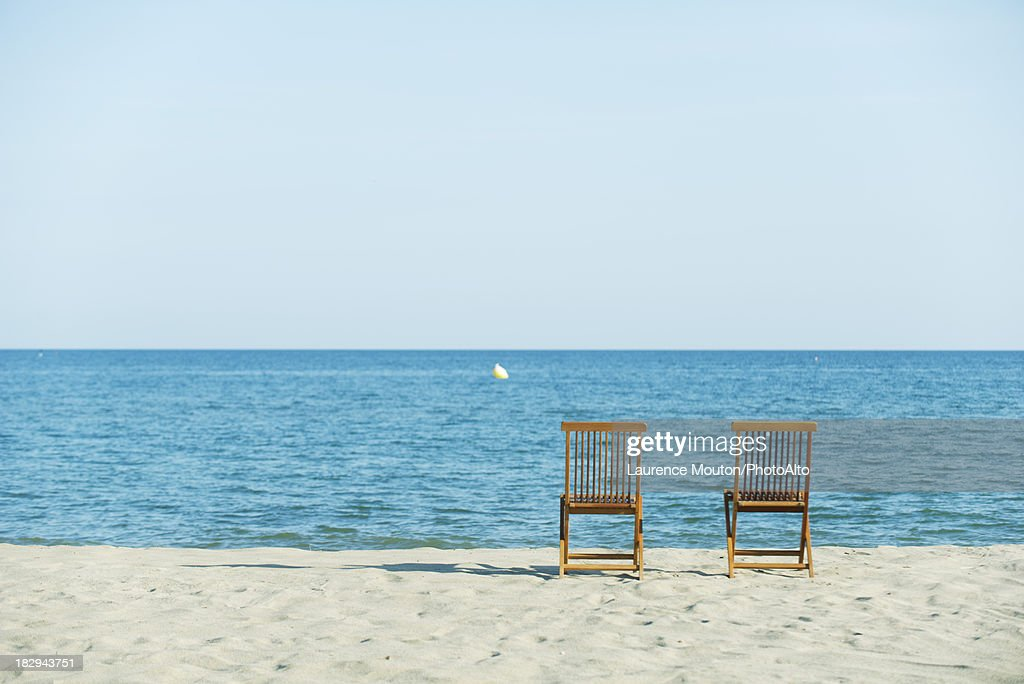 Lounge chairs on beach, rear view : Stock Photo