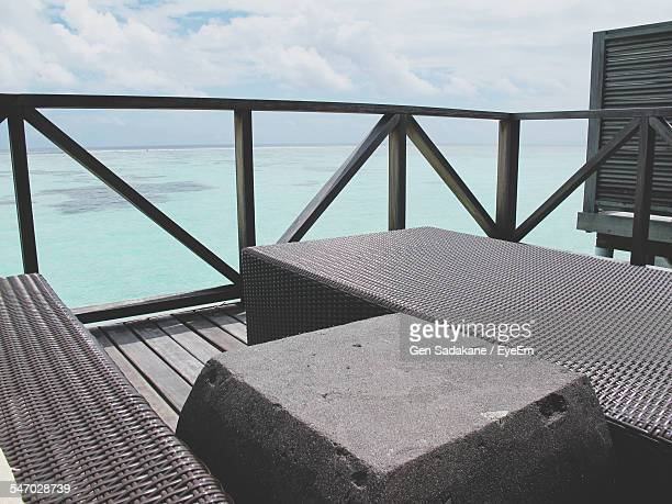 Lounge Chairs On Wooden Terrace At Seashore