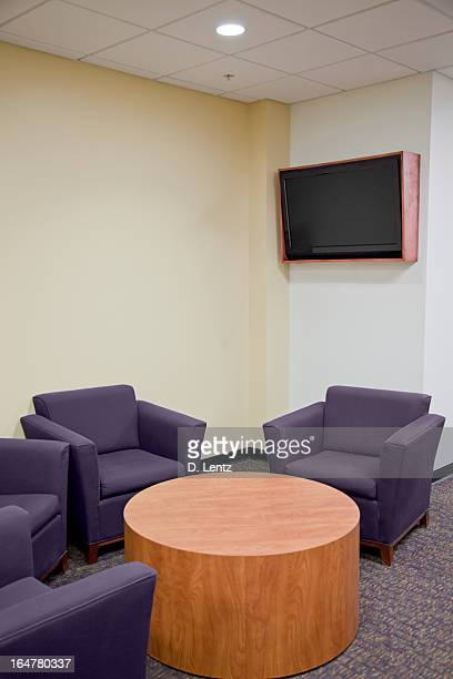 Lounge with four purple sofas and a round wooden table
