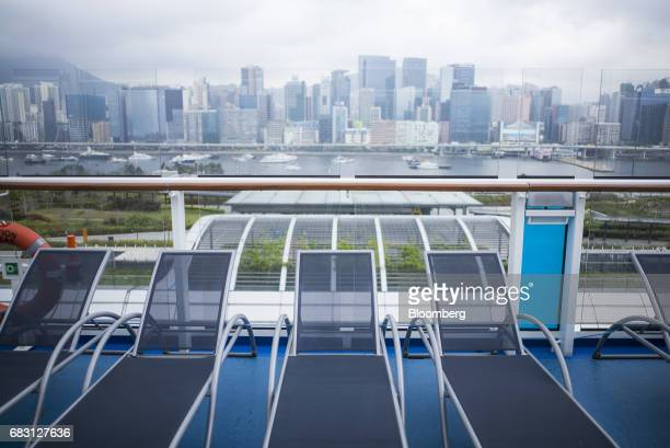 Loungers sit on the deck of the Ovation of the Seas Quantumclass cruise ship operated by Royal Caribbean Cruises Ltd at the Kai Tak Cruise Terminal...