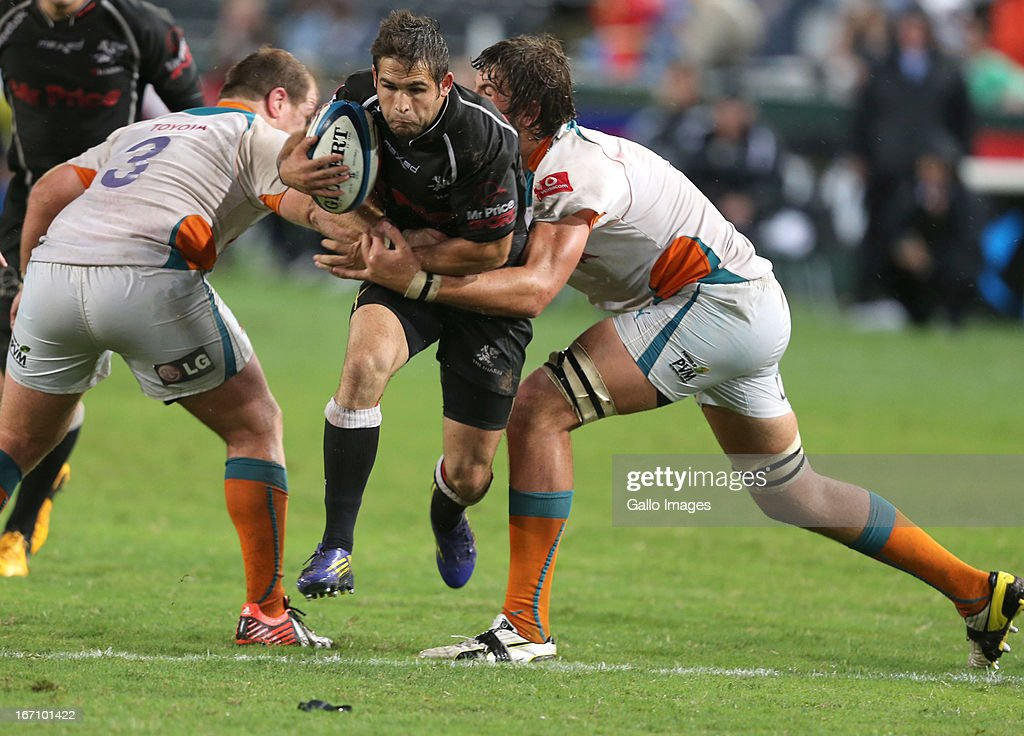 Lourens Adriaanse and Lodewyk de Jager tackle Cobus Reinach during the Super Rugby match between The Sharks and Toyota Cheetahs from Kings Park on April 20, 2013 in Durban, South Africa.