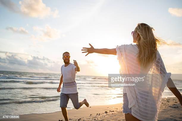 愛、情熱-若いカップルはビーチサンセットに