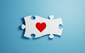 White puzzles forming a heart shape on blue background. Horizontal composition with copy space. Great use for find love concepts.