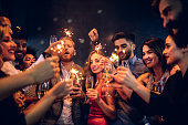 Group of people celebrating with champagne and sparklers