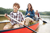 A young boy enjoying a kayak ride out on the lake with his parents