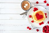 Pancakes with jam in shape of heart, hot chocolate and raspberries over white wood. Love concept with copy space.